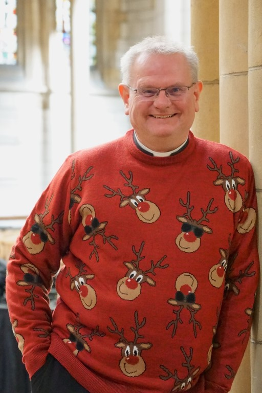Dean Roger standing inside Truro Cathedral wearing a Christmas jumper