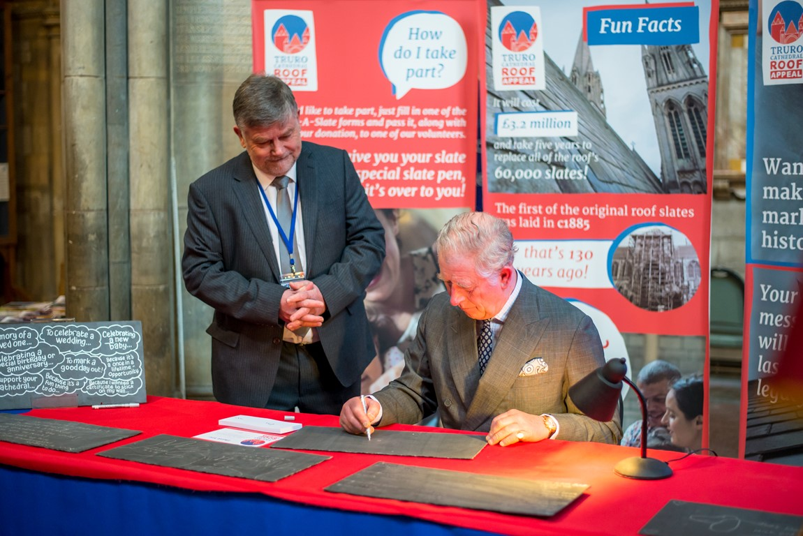 Kevin Bray standing whilst a seated Prince Charles sits at a table and signs a slate in support of Truro Cathedral's roof appeal.  Banners for the roof appeal can be seen in the background.