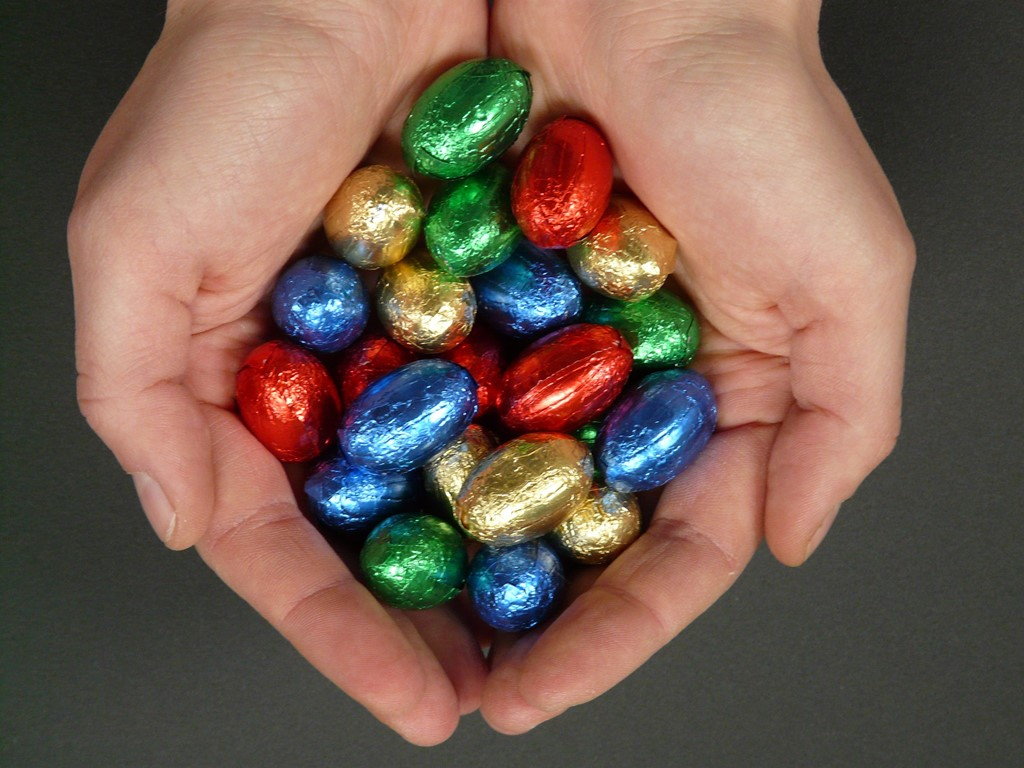 Two hands cupping lots of small chocolate easter eggs in bright coloured foils