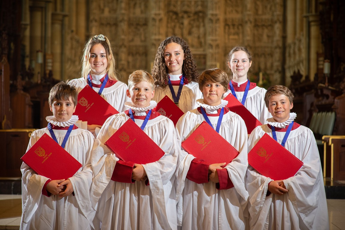 Photograph of 7 new Head Choristers of Truro Cathedral Choir posed in front of the reredos.