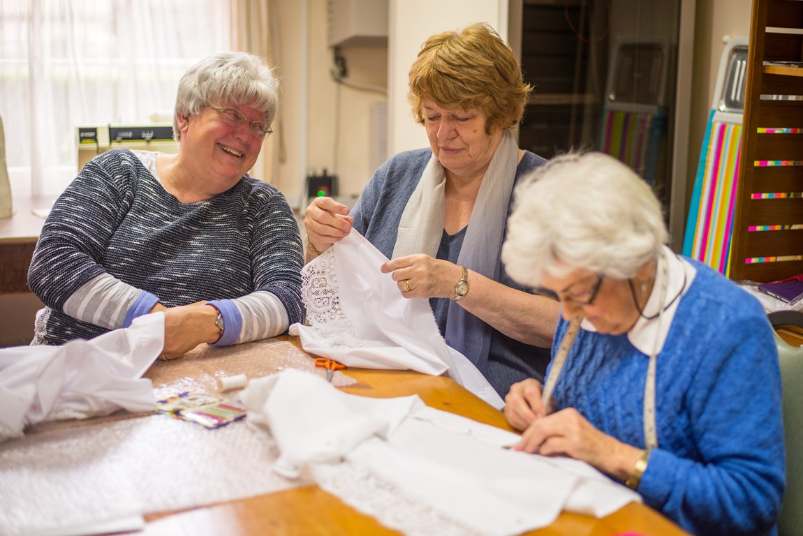 Three ladies from the Truro Cathedral volunteer Sewing Guild sat at a table sewing.