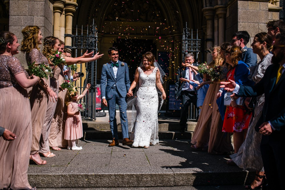 Bride and groom leaving the cathedral as guests throw confetti over the newlyweds.