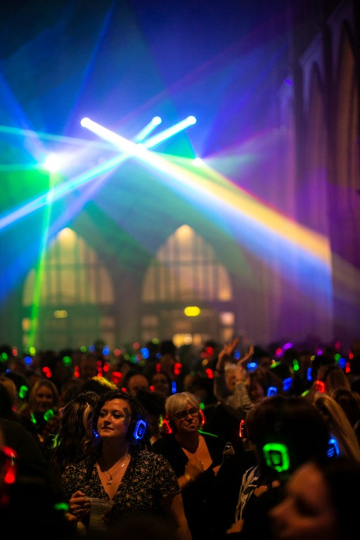 Crowds inside Truro Cathedral at the silent disco dancing beneath lasers