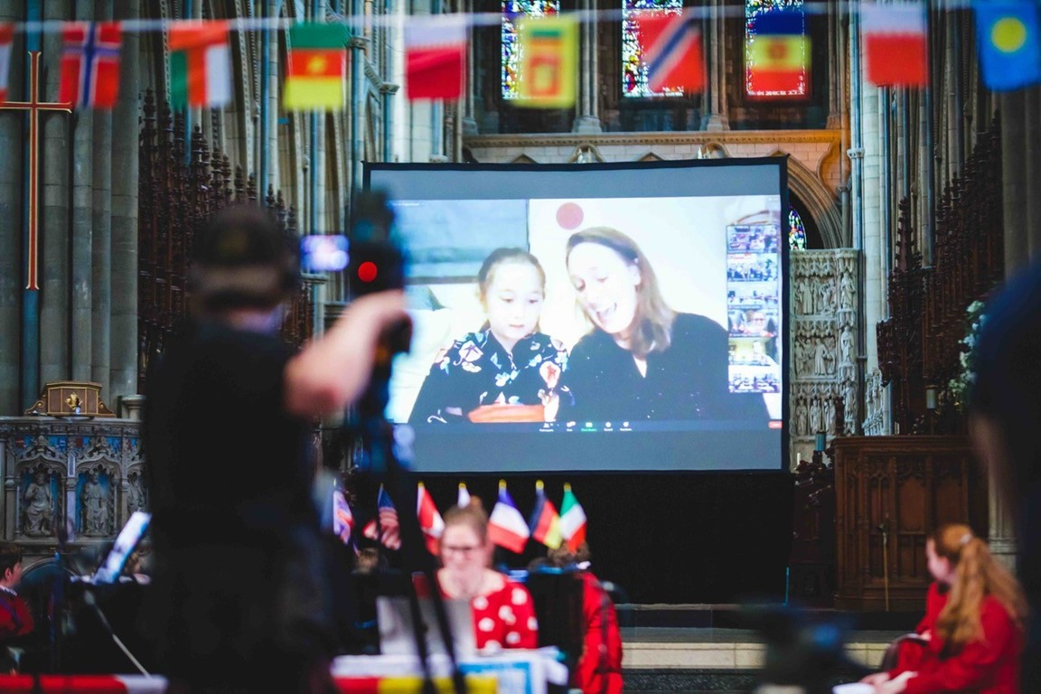 Little girl and adult on large projection screen in Truro Cathedral taking part in zoom event