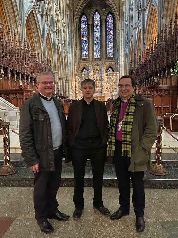 Reverend Hugh Nelson, Dean Roger and the Bishop of Truro standing in front of the high altar inside Truro Cathedral