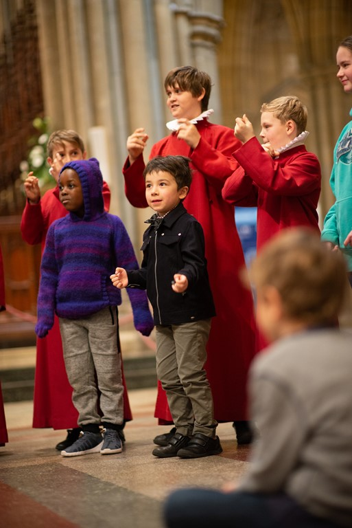 Truro Cathedral choristers in cassocks clicking  their fingers with younger children joining in