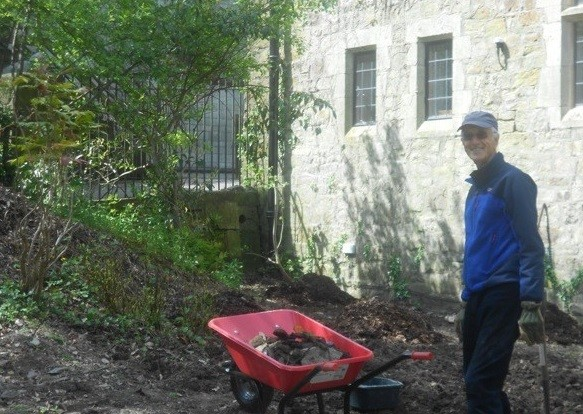 Volunteer standing with wheelbarrow outside cathedral