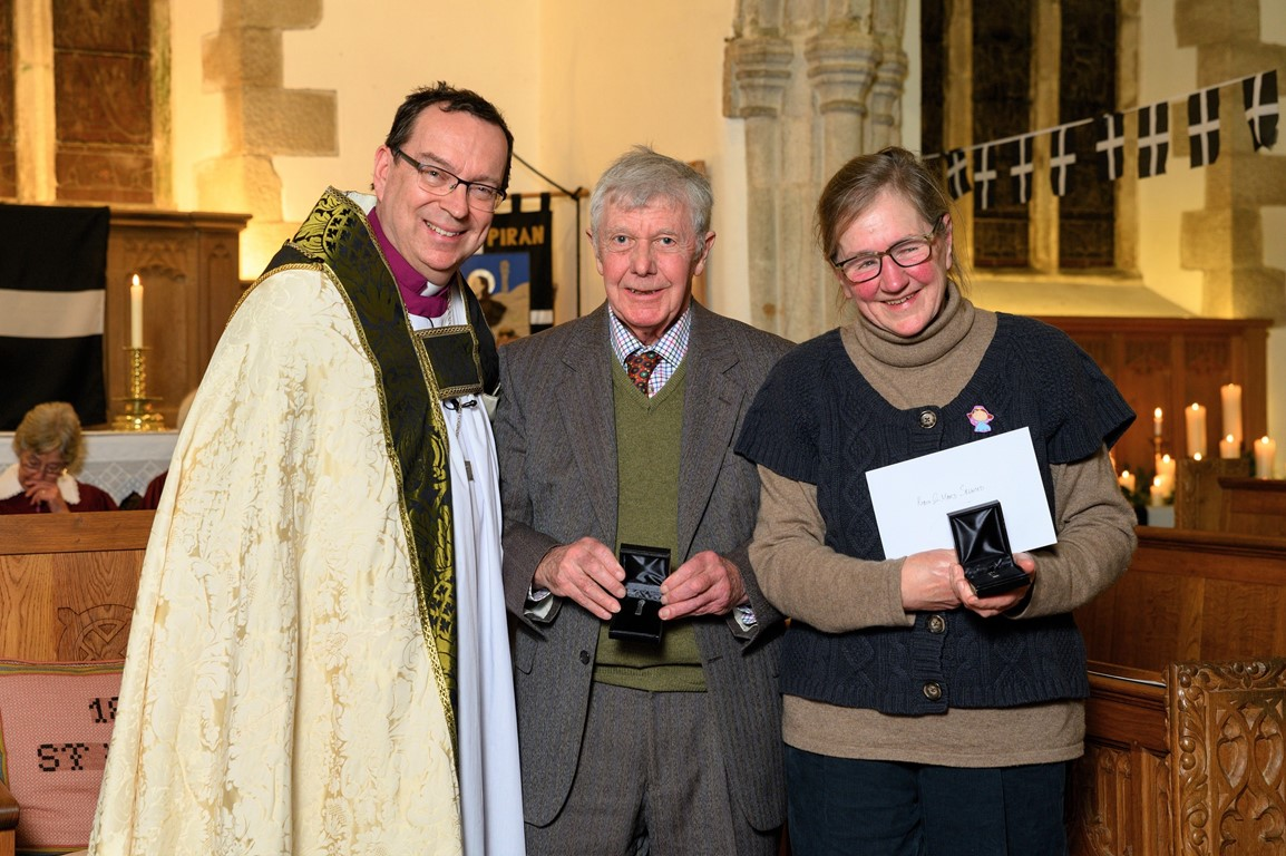 Robin and Mard Sellwood receiving their Cross of St Piran award from Bishop Mounstephen