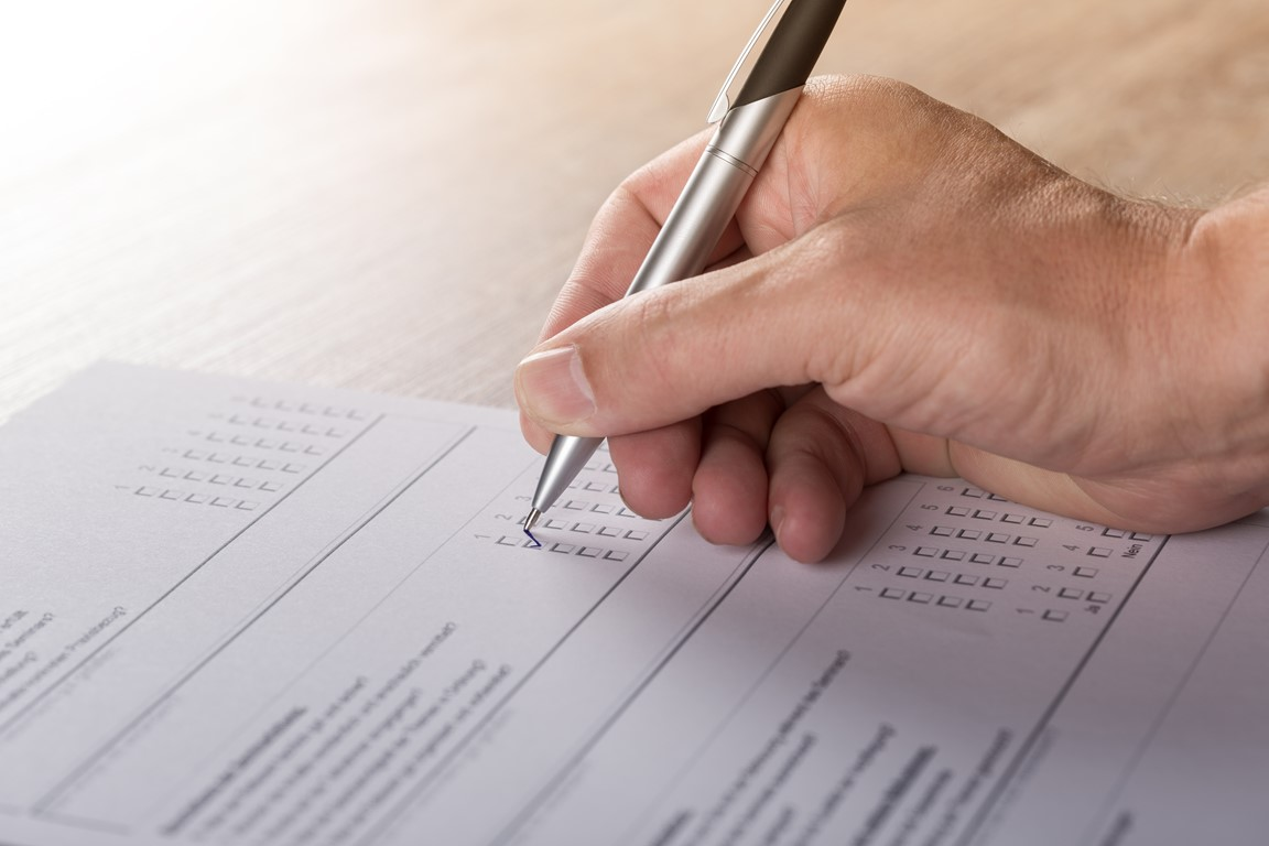Close up image of someones hand holding a pen and filling out a survey