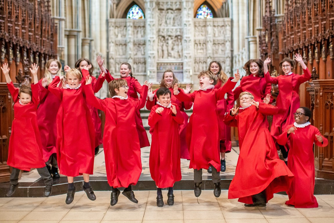 Truro Cathedral Choristers in red Cassocks jumping in the air in front of the altar of Truro Cathedral