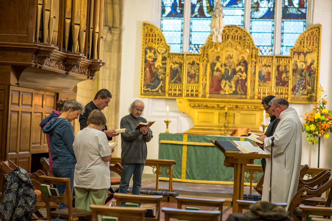 People standing in prayer at Truro Cathedral